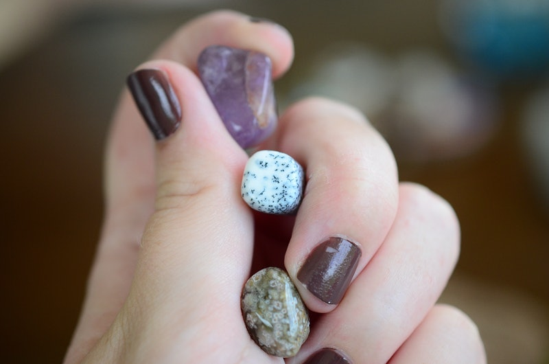 Amethyst, Dendritic Agate, and Ocean Jasper. Small sized crystal bundle. Woman's hand holding healing crystals. Crystals with intricate detail, macro photo of stones with natural lighting.  Tree agate