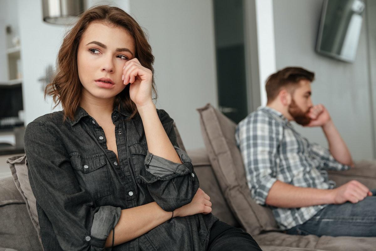 Photo of young sad quarrel loving couple sitting on sofa indoors. Looking aside.