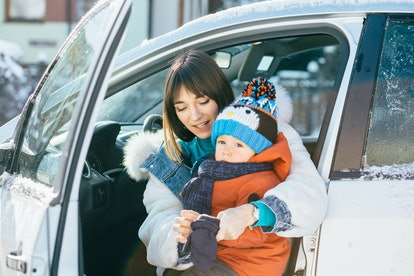 Happy family concept. Young mother on driver's seat of car and trying to wear mittens her cute toddl...