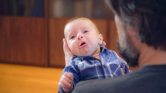 Handsome man with beard holding son. Crying baby in father s arms. Newborn with dad.