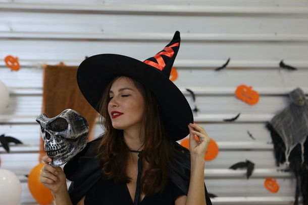Halloween Witch with a  mask. Beautiful young surprised woman in witches hat and  holding mask.