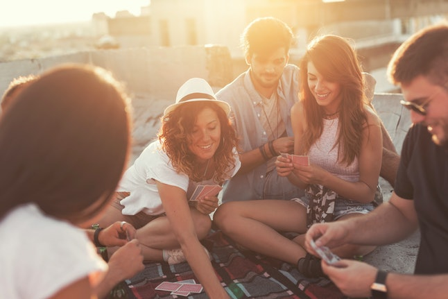 Group of young people sitting on a picnic blanket, having fun while playing cards on the building rooftop. Focus on the couple in the middle