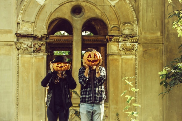 young halloween couple man and girl in black witch hat near old ruined building with traditional autumn holiday symbol of orange spooky pumpkin outdoor