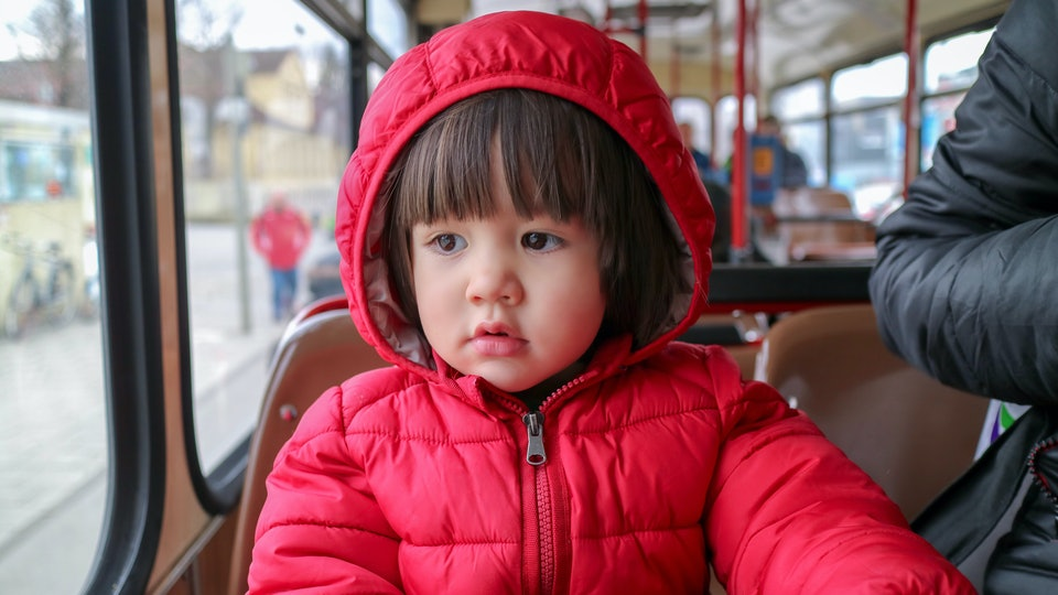 Little cute boy sitting on the bus looking out the window. he wearing red jacket with hooded