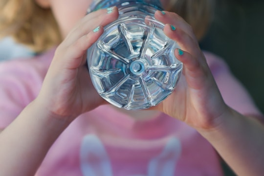 Close-up of a girl wearing a pink shirt drinking water out of a plastic bottle