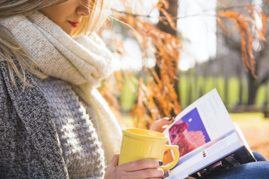 Female reading in fall forest