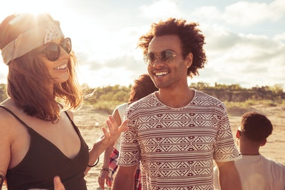 Image of happy young loving couple friends walking outdoors on the beach talking with each other.