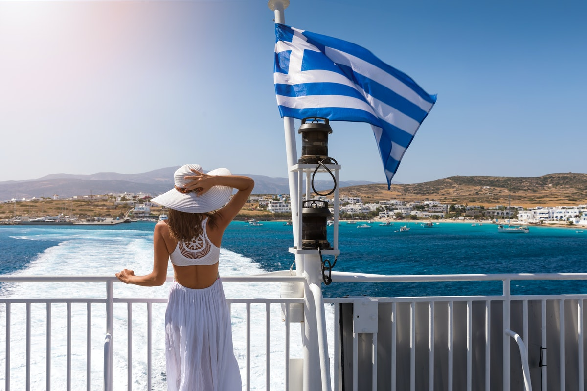 Woman in a white dress next to to a Greek flag on a ferry boat in the aegean sea, Greece