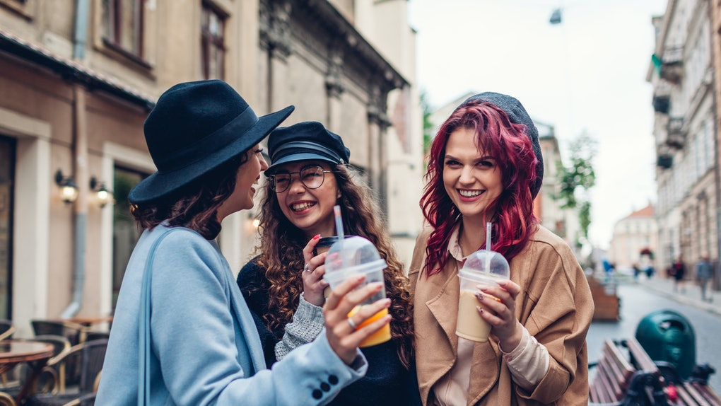 Three stylish women drink out of to-go cups and laugh while hanging out outside a café on Thanksgiving break.