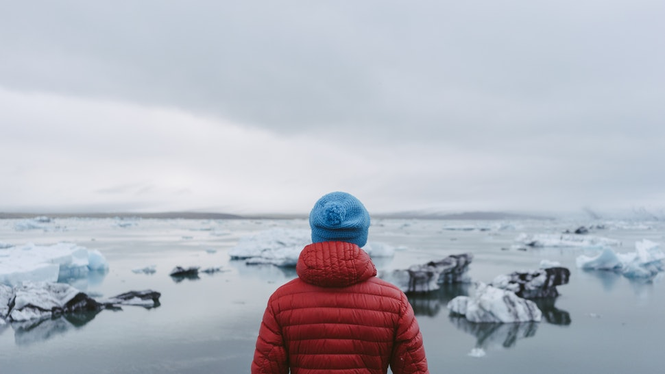 Man standing on the shore of a glacier lagoon.
