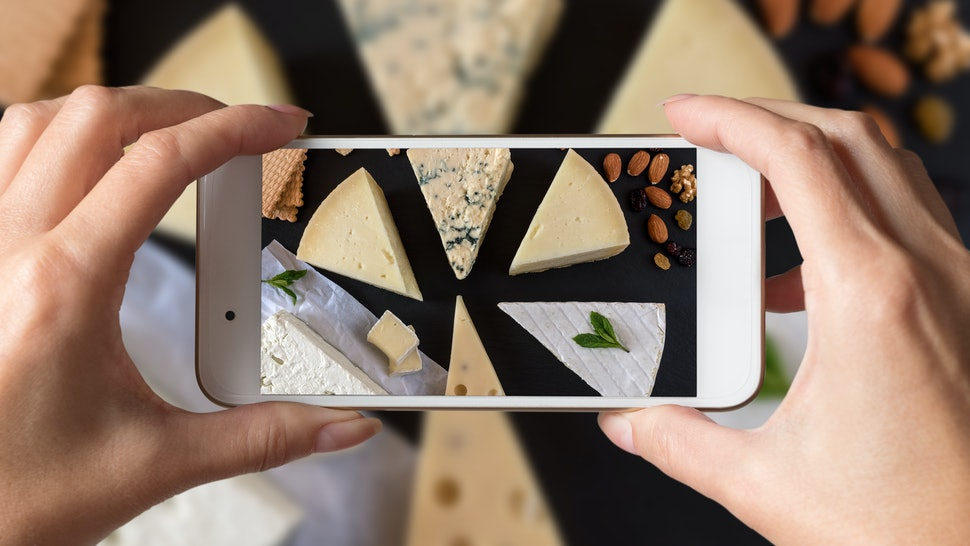 Woman hands taking a photo of different kinds of cheeses on black stone board with nuts and herbs.