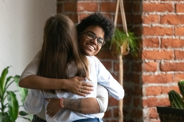 Smiling African American woman hugging, embracing with female best friend, saying hello, greeting each other at meeting in cafe, reunion, friendship support concept, having good relations