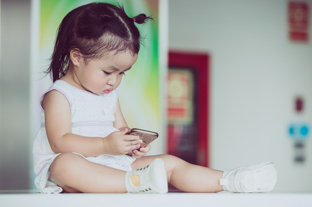 Little baby girl playing smartphone cause ADHD, 1-2 year old