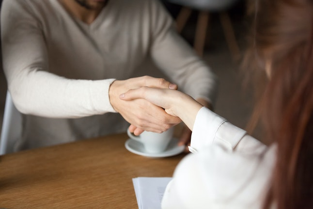 Close up of husband shake hand of broker closing deal about house purchase meeting out in café, man handshake realtor or agent making agreement about mortgage or loan, couple sign insurance contract