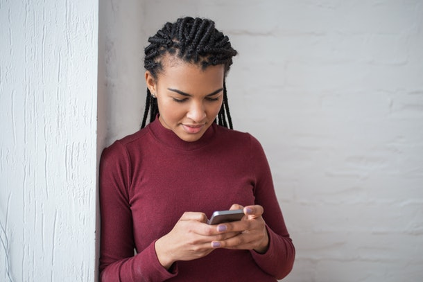 Content Black Woman Texting on Smartphone by Wall