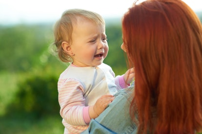 Crying daughter sitting on mother's hands during sunny day in the field. Young mom trying to calm down little baby, talking to her. Woman having red hair, wearing jeans shirt.