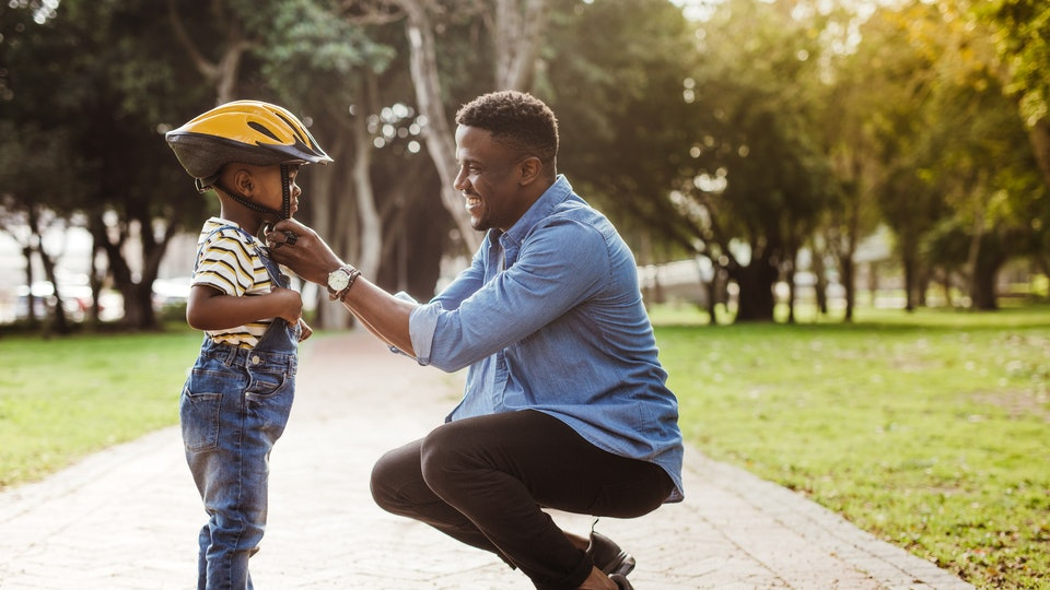 African man putting helmet on cute boy at the park. Father puts his son a protective helmet for riding bike.