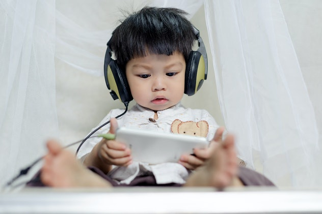 cute little Baby Boy enjoying watching and listening Music form smart phone with head phones,holding in hands the smartphone