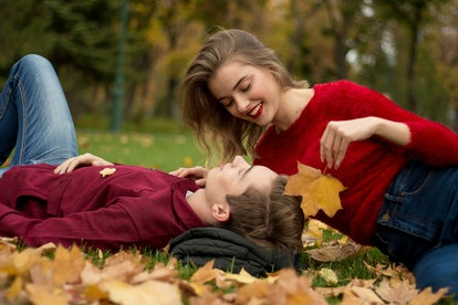 the girl and the guy in red sweaters and jeans sit in the park on the green grass in the yellow maple leaves, the girl smiles.a date in the fall.Leaves a leaf against the face of a man, protection,