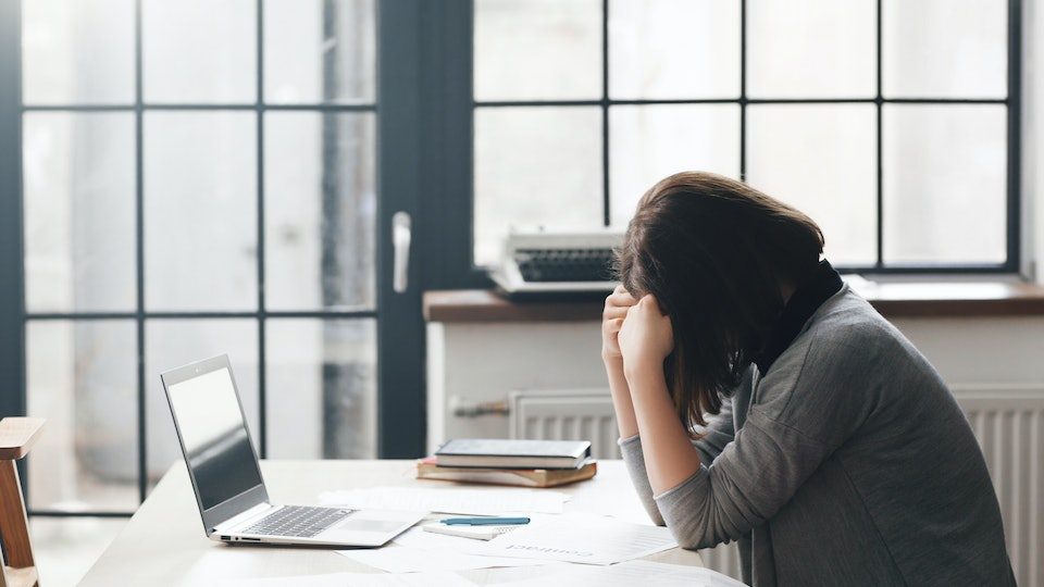 Female entrepreneur sitting in office and looks confused with laptop on desk. Business problems, crisis, bankruptcy concept