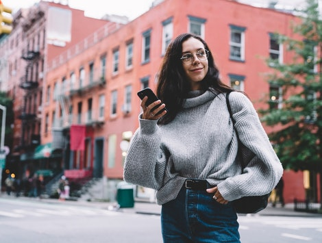 Beautiful slim smiling woman in glasses with black bag wearing denim and sweater looking away and browsing smartphone on city street