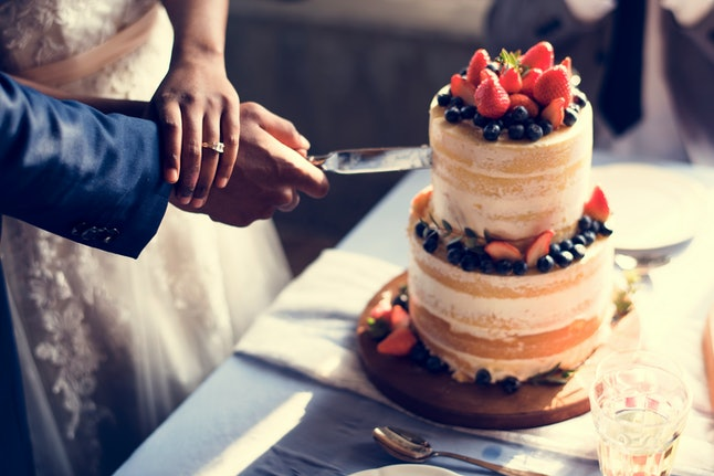 Couple Hands Cutting Wedding Cake