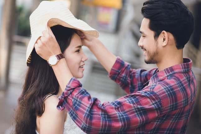 Couple take care together or husband put the hat to his wife or lover looking together and has eye contact