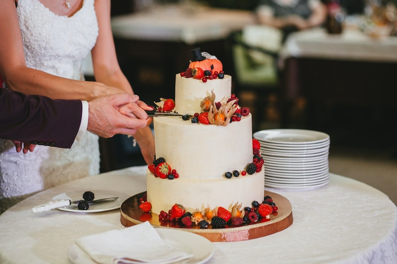 The bride and groom cut a beautiful wedding white cake decorated with berries, fizalis and pumpkins. Horizontal