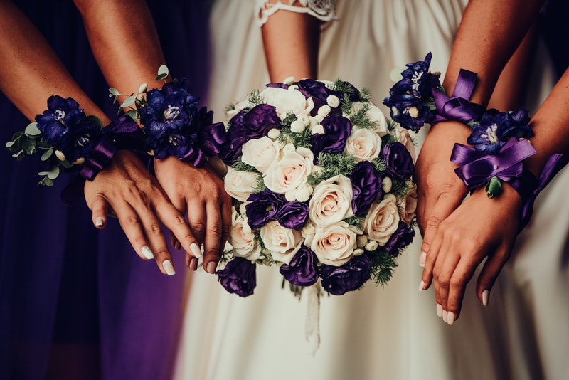 Bride with bridesmaids hand with beautiful flowers
