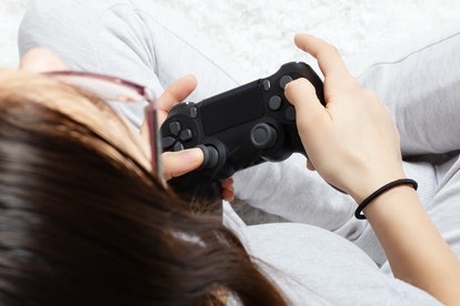 Female hands hold joystick, a young girl plays a video game