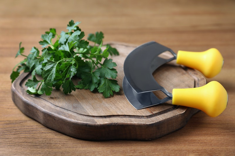 Cutting board with parsley and mezzaluna knife on wooden table
