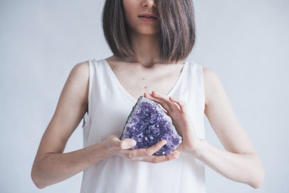 This woman holding an amethyst could pair the crystal with lavender essential oil to de-stress.