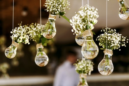 Original wedding floral decoration in the form of mini-vases and bouquets of flowers hanging from th...
