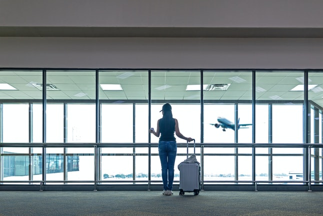 Traveler women plan and backpack see the airplane at the airport glass window, Asian tourist hold bag and waiting near luggage in hall airplane departure. Travel Vacation Concept.