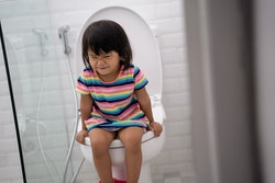 portrait of toddler push it hard while pooping in the toilet