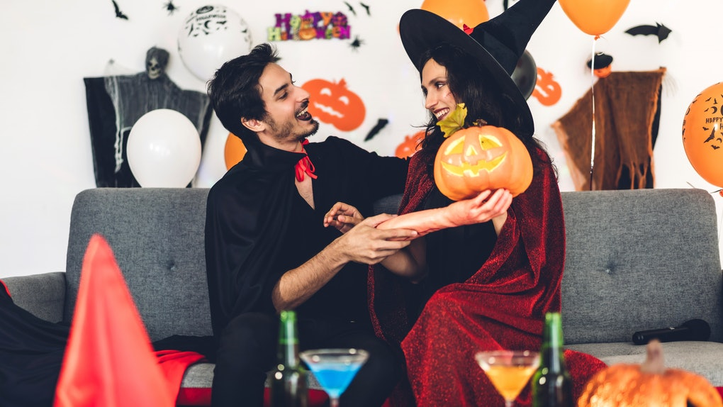 Couple having fun holding pumpkins and wearing dressed carnival halloween costumes and makeup posing with bats and balloons on background at the halloween party.Halloween holiday celebration concept