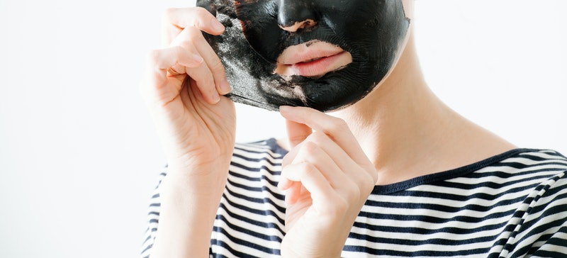 Young woman in striped half sleeve removing bamboo charcoal peel off facial mask at home. Over white background. Cropped chin and hands.