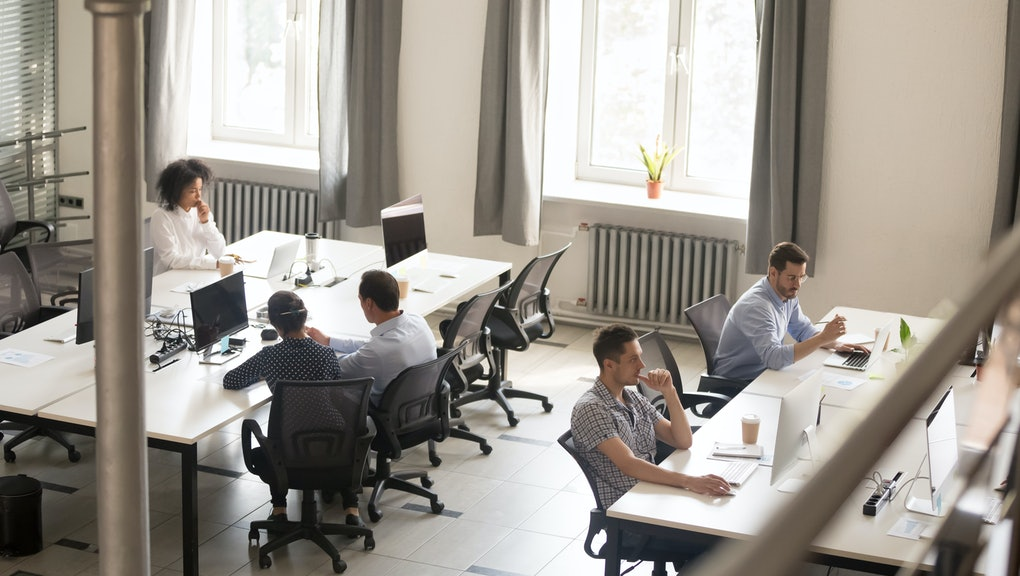 Top view of diverse people working together on computer performing daily routine tasks in coworking space, multiracial millennial men and women busy using devices discussing projects in shared office