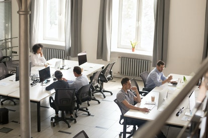 Top view of diverse people working together on computer performing daily routine tasks in coworking ...