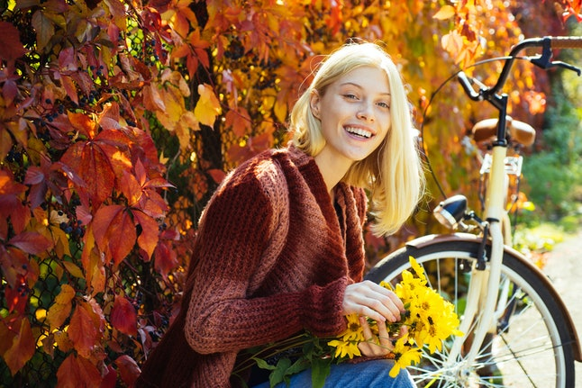 Autumn woman in autumn park with red pullover. Beautiful Autumn Woman with Autumn Leaves on Fall Nature Background. Pretty tenderness model looking at camera