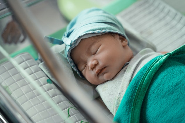 Asian newborn baby laying in crib in the hospital