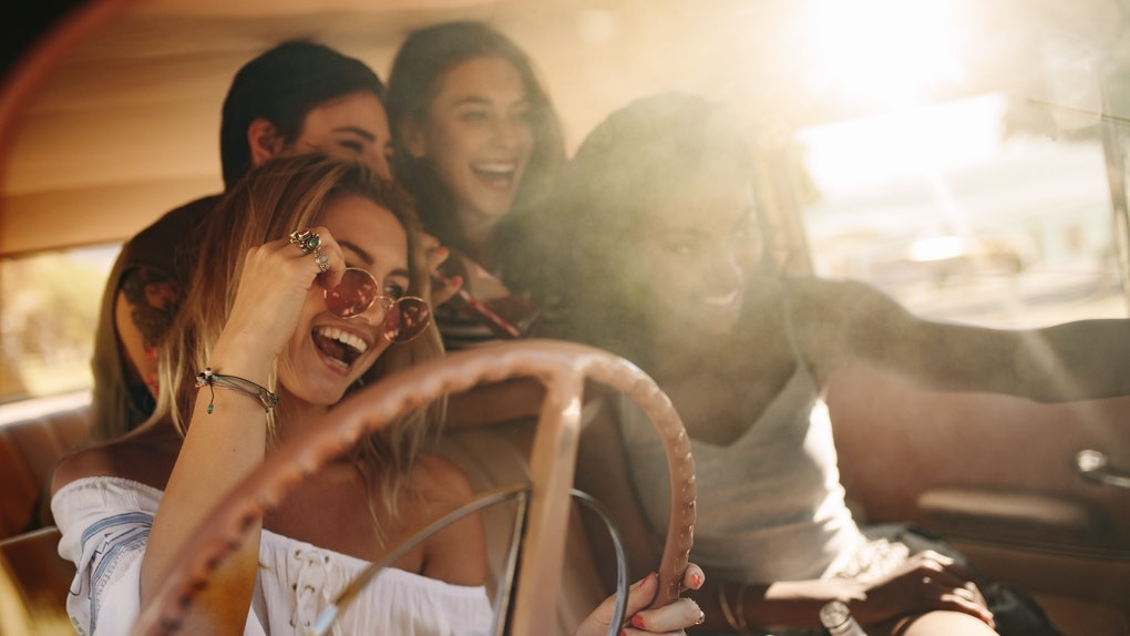 Friends on road trip posing for the selfie inside the car. Group of young women enjoying on the road trip.