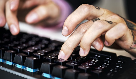 Hands with tattoo typing on a keyboard
