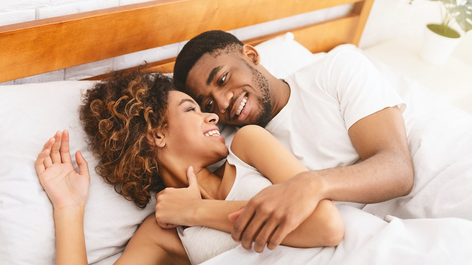 Happy morning together. Millennial african-american couple smiling to each other in bed, free space