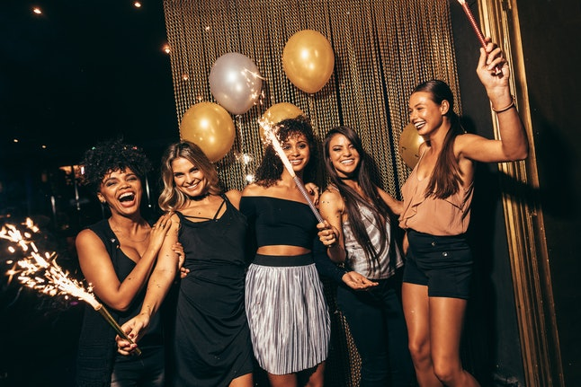 Group of women with fireworks at party. Stylish girls enjoying party at nightclub.