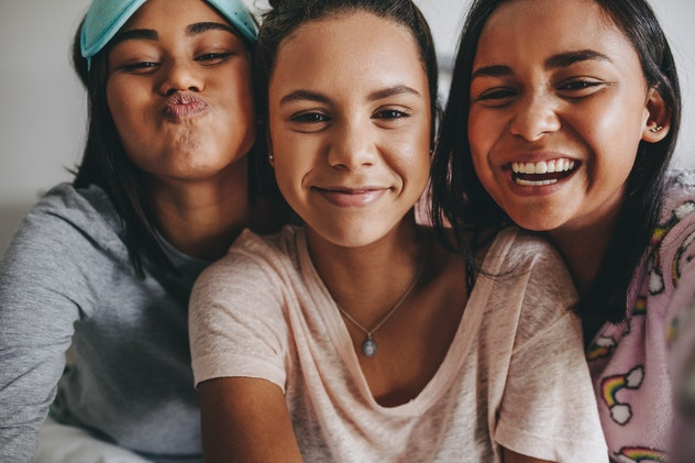 Three young girls sitting together posing for a selfie during a sleepover. Girls having a good time during a sleepover.
