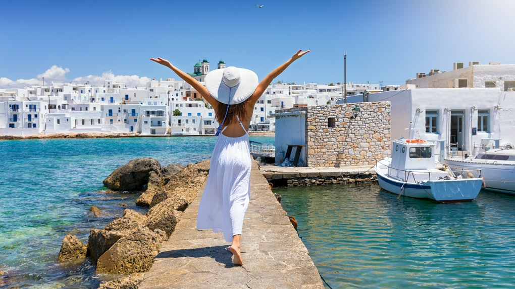 Happy traveller woman enjoys her summer vacation time on the island of Paros, Naousa village, Greece