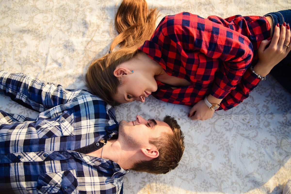 Stylish young couple in shirts and jeans while walking along the lake shore. A beautiful attractive girl and her handsome boyfriend lying on a blanket and smiling to each other. Close up.
