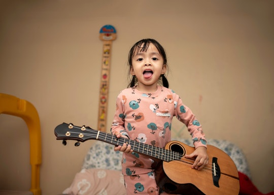 Little girl rock star in pajamas with Ukulele.and she making a tongue out in the living room