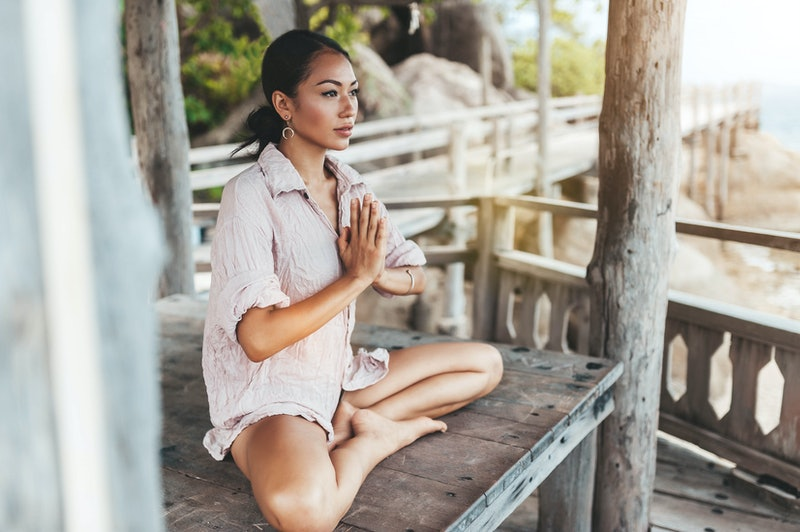 Young woman meditating in a yoga pose in a gazebo at the beach